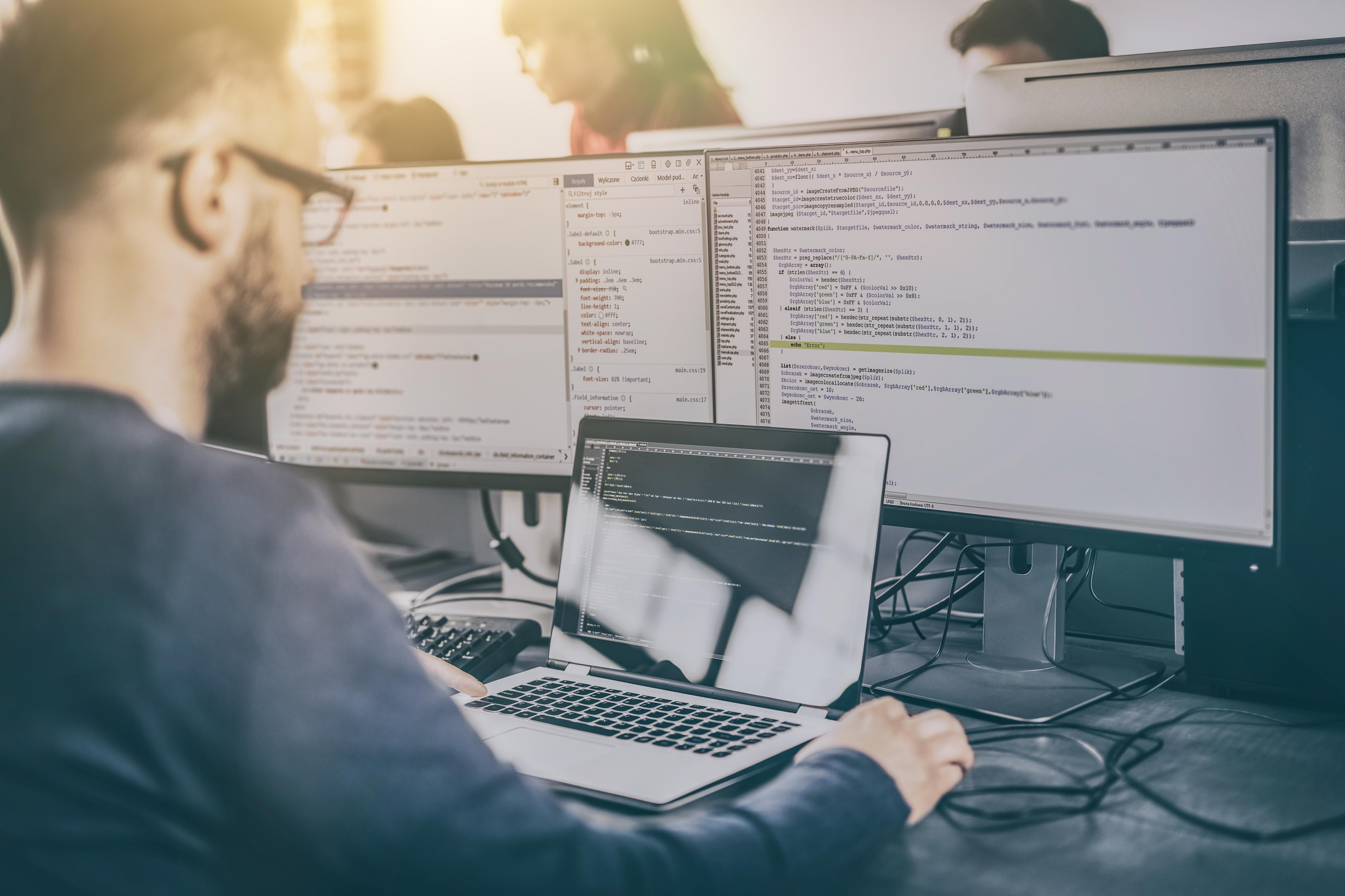 PHP-Entwickler mit Laptop und Monitor